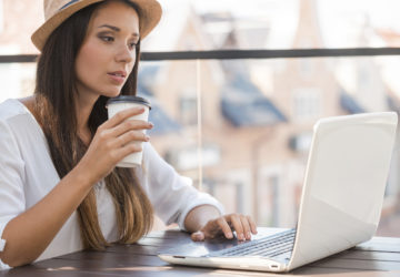 Working outdoors. Beautiful young woman in funky hat working on laptop and smiling while sitting outdoors
